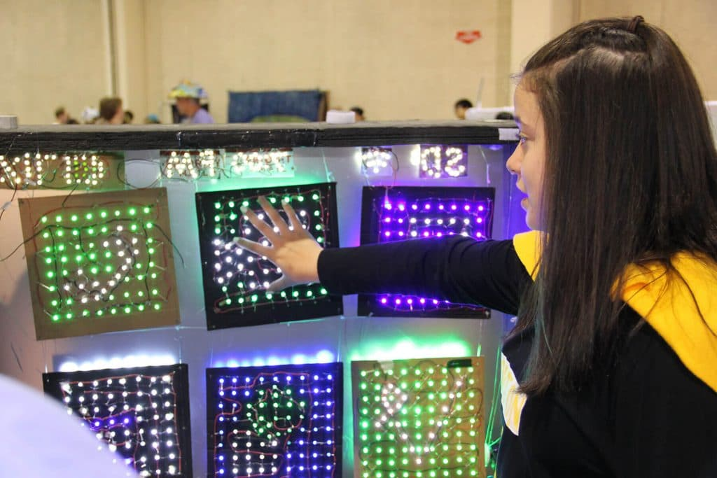 Student explaining her solution to a Destination Imagination tournament official